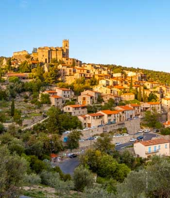 Town perched up a mountain topped by a castle in Pyrenees-Orientales