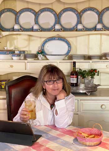 Woman smiles into a tablet, holding a glass of brandy and ginger ale
