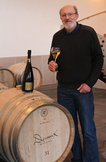 Man stands by a wooden wine barrel holding a large glass of Champagne