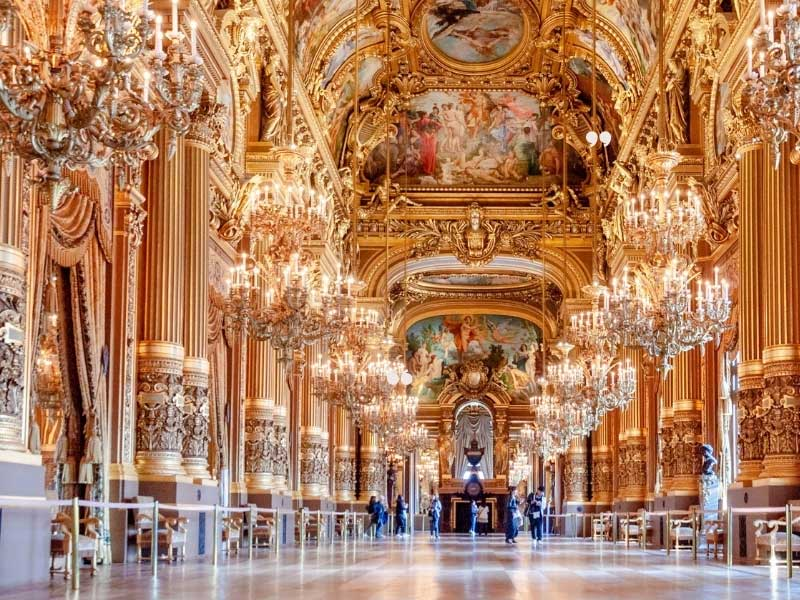 Gilded hallway of the Opera National in Paris, golden columns and plasterwork lit by chandeliers