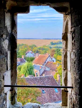 View through an ancient stone window over the countryside and village of Provins