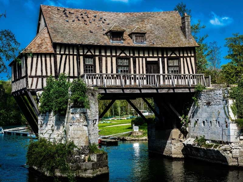 Half timbered medieval mill house on a broken bridge over the Seine river at Vernon