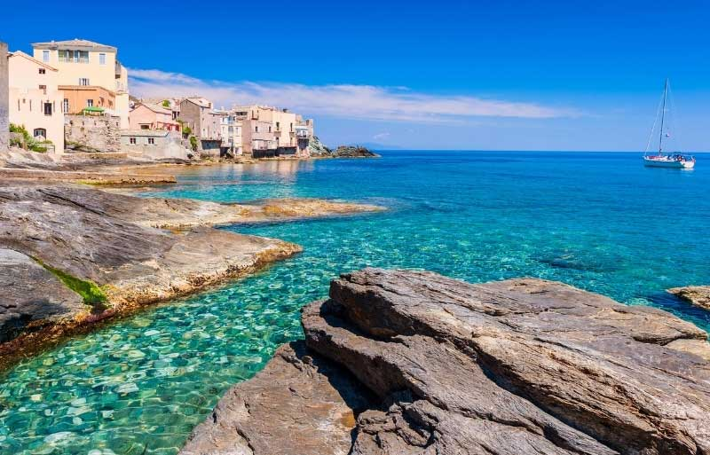 View of a town at the edge of the crystal clear turquoise coloured sea on the island of Corsica